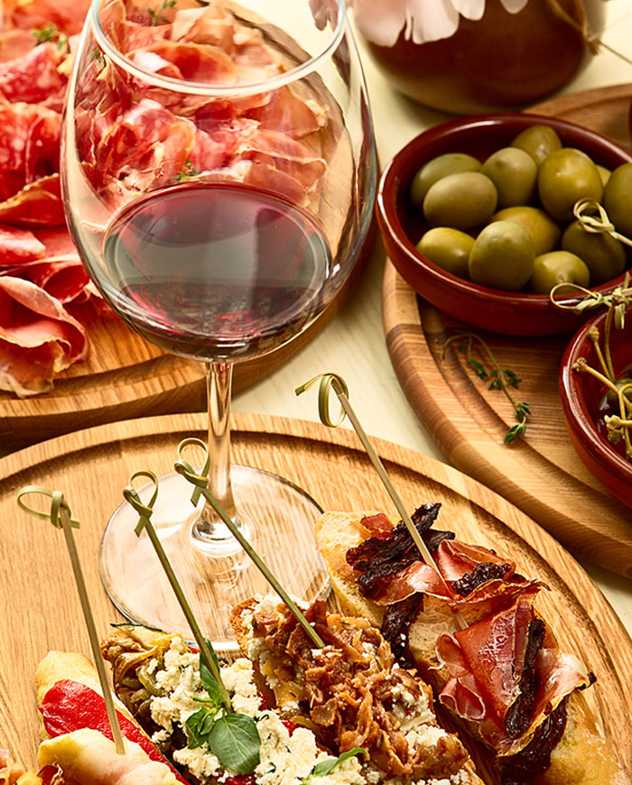 Tapas on board with wine glass