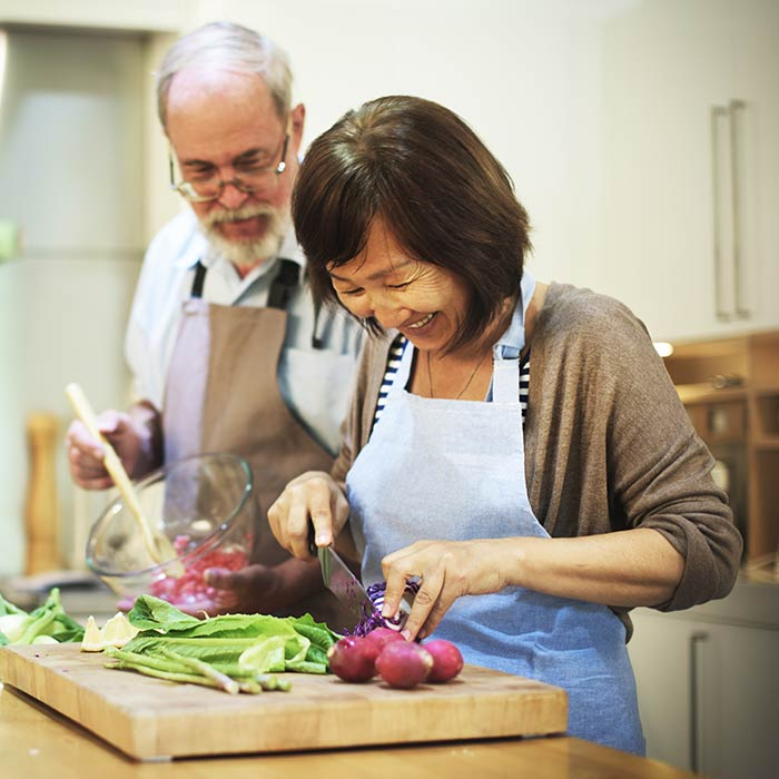 Mature man and woman chopping vegetables