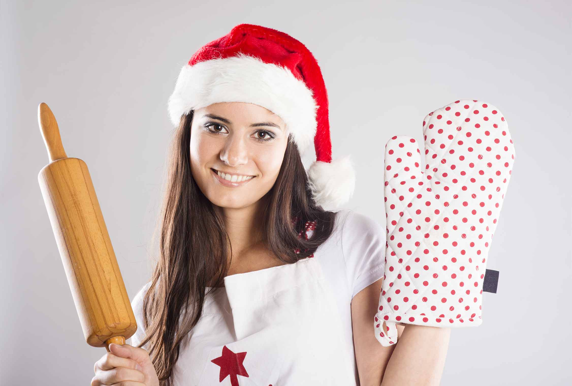 Girl with Christmas hat, oven glove and rolling pin